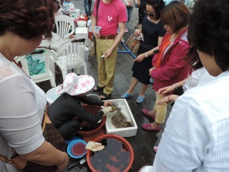 Jeju woman diver, probably in her 80s, selling her gathered seafood